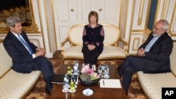 FILE - US Secretary of State John Kerry, former EU Foreign Policy Chief Catherine Ashton and Iranian Foreign Minister Mohammad Javad Zarif meet for talks on the sidelines of nuclear talks with Iran aimed at settling a dispute over Iran's nuclear program at the Palais Coburg in Vienna on Saturday Nov. 22, , 2014.