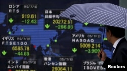 Papan elektronik memasang informasi indeks saham dari berbagai negara, di Tokyo, Jepang (6/7).