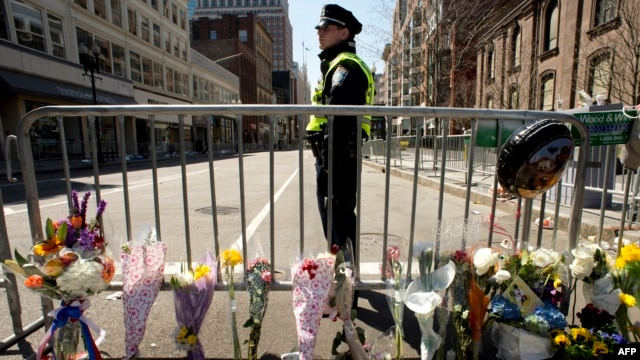 Boston police officer stands guard at a memorial site at Boylston and Arlington streets along the course of the Boston Marathon on April 16, 2013, a few blocks from where two explosions struck near the finish line.
