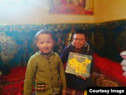 """汉人""""大哥哥""""给维吾尔儿童送来图书《我们的中国》(白道仁提供)"""