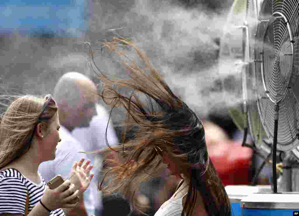 A spectator cools herself at a water spraying fan at the Australian Open tennis championships in Melbourne, Australia.