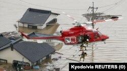 امدادی اہلکار جاپان کے جنوبی علاقے کوراشیکی میں سیلابی پانی میں گھرے ایک گھر کے رہائشیوں کو ہیلی کاپٹر کے ذریعے ریسکیو کر رہے ہیں۔