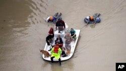 Evacuados se abren paso entre las inundaciones cerca de Addicks Reservoir mientras las aguas desbordadas por Harvey crecen el martes, 29 de agosto de 2017.