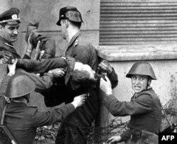 Doğu Almanya askerleri, 17 Ağustos 1962'de, Batı'ya kaçmaya çalışırken öldürdükleri Peter Fechter'in cesediyle