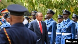 Kenyan President Uhuru Kenyatta inspects a guard of honor as he arrives at the Parliament Building to deliver his state of the nation address in Nairobi, March 27, 2014.