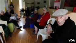 Elderly men and women evacuated from their homes, sit in a classroom of a kindergarten in Mirabello, Italy