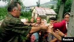 ARHIVA - Komandant vojske bosanski Srba Ratko Mladić, pruža hranu bosanskim muslimanima, izbeglicama iz Srebrenice 12. jula 1995. (Foto: Reuters)
