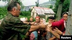 Prvostepeni ratni osuđenik Ratko Mladić deli hranu bošnjačkoj populaciji u Potočarima; 13. jul 1995.