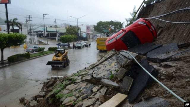 A car lies on its side after a portion of a hill collapsed due to heavy rains in the Pacific resort city of Acapulco, Mexico, Sept. 15, 2013.