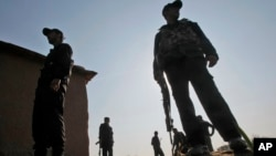 FILE - Pakistani policemen stand at the site of an attack, on the outskirts of Peshawar, Pakistan, Feb. 12, 2014.