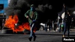 Un manifestant palestinien court pendant les affrontements avec les troupes israéliennes, près de la colonie juive de Beit El, près de Ramallah. 8 décembre 2017.