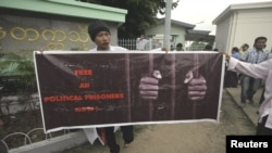 A man holds a poster calling for the freedom of political prisoners in front of the Rangoon University where U.S. President Barack Obama was giving a speech, November 19, 2012.