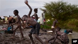 In this photo taken Thursday, June 5, 2014, displaced children wash themselves on the muddy bank of a river just outside the United Nations base which has become home to thousands of those displaced by recent fighting, in the town of Malakal, Upper Nile State, South Sudan.