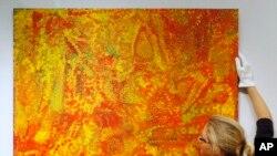 Pegawai rumah lelang Christie's Rhiannon Broomfield berpose di sebelah lukisan tanpa judul karya seniman Aborigin Emily Kame Kngwarreye yang dipajang di lelang Modern and Contemporary Australian Art.