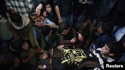 ພວກໄວ້ທຸກພາກັນນັ່ງອ້ອມສົບ ຂອງຜູ້ນໍາກຸ່ມຫົວຮຸນແຮງ Islamic Jihad ໃນພິທີ່ສົງສະການທີ່ເຂດ Gaza, ວັນທີ 10 ມີນາ 2012.