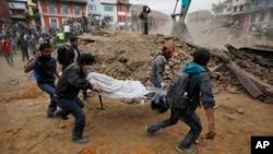 지진이 강타한 카트만두에서 자원봉사자들이 토사에 파묻힌 희생자를 구조해 옮기고 있다.