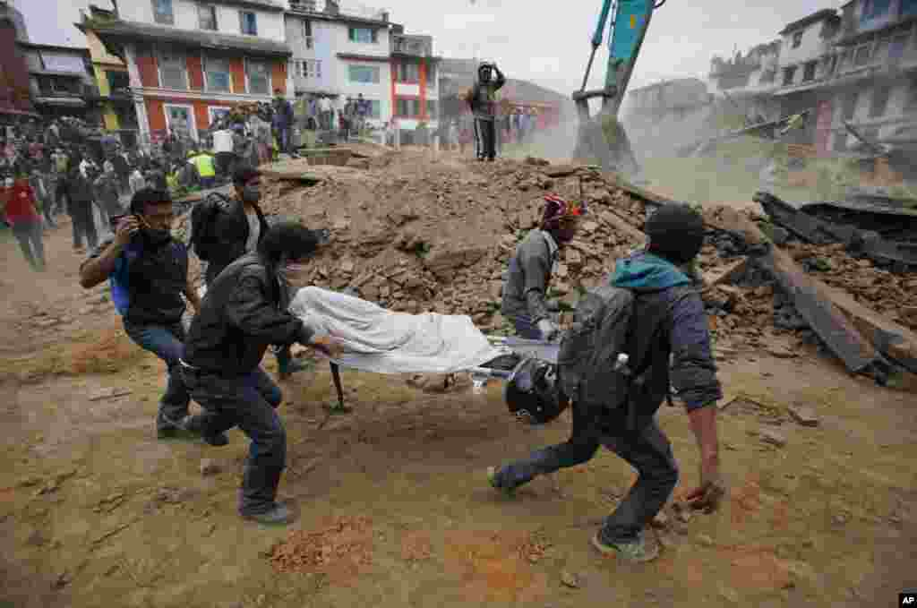 Volunteers carry the body of a victim on a stretcher after an earthquake in Kathmandu, Nepal, April 25, 2015.