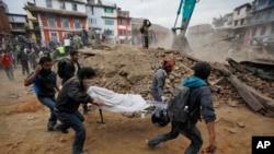 Beberapa sukarelawan membawa tandu berisi mayat korban gempa yang ditemukan diantara reruntuhan bangunan yang ambruk setelah gempa di Kathmandu, Nepal, 25 April 2015. (AP Photo/ Niranjan Shrestha)