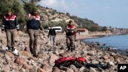 土耳其军警站在恰纳卡莱省艾瓦哲克城附近海滩上的一名移民尸体旁。(2016年1月30)