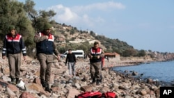 Petugas paramiliter Turki berdiri dekat jenazah migran di pantai dekat kota Ayvacik, Canakkale, Turki, 30 Januari 2016.