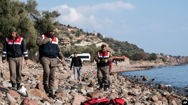 Turkish paramilitary police officers stand near a dead body of a migrant on the beach near the Aegean town of Ayvacik, Canakkale, Turkey, Jan. 30, 2016.