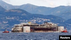 Буксир тянет лайнер Costa Concordia в порт Генуи в Италии, где он будет разобран на металлолом. 27 июля 2014 г.