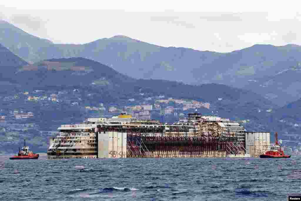 Tug boats tow the Costa Concordia ship as they arrive outside Genoa's port, in northern Italy, where the ship will be broken up for scrap.