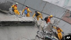 Các nhân viên cứu hộ tìm kiếm người sống sót tại tòa nhà 17 tầng đổ sập trong trận động đất mạnh 6,4 độ richter hôm 6/2.