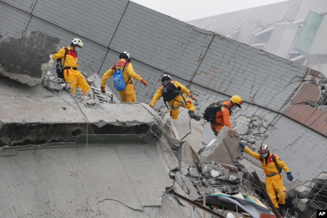 Rescue workers search a collapsed building from an early morning earthquake in Tainan, Taiwan, Saturday, Feb. 6, 2016.