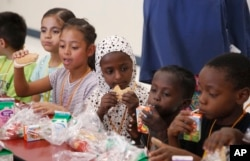 From left to right, students Vania Lopez Lopez, Genesis Yol, Kediga Ahmed, Mussa Ahmed, and Kiza Lulaca, eat lunch at Valencia Newcomer School Thursday, Oct. 17, 2019, in Phoenix. (AP Photo/Ross D. Franklin)