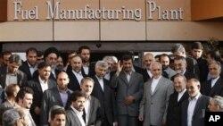 ປະທານາທິບໍດີອິຣ່ານ ທ່ານ Mahmoud Ahmadinejad, ໂບກມືໃຫ້ສື່ມວນຊົນ ຫລັງຈາກພິທີ ເປີດໂຮງງານຫລອມເຊື້ອໄຟນີວເຄລຍຂອງອິຣ່ານ ທີ່ Isfahan ໃນປີ 2010.
