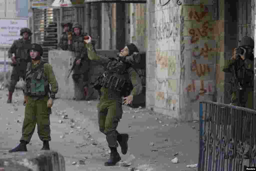 An Israeli army soldier throws a sound grenade at Palestinians during clashes following the funeral of 19-year-old Palestinian student Hadeel al-Hashlamun in the occupied West Bank city of Hebron. The Israeli military said troops shot al-Hashlamun as she tried to stab a soldier. But relatives of al-Hashlamun denied the Israeli report saying she was executed. In a picture posted on Facebook, a soldier could be seen aiming his rifle at a woman said to be Hashlamun, standing a short distance away. She was completely covered in a black robe.