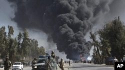 阿富汗防暴警察從遠處戒備﹐憤怒的阿富汗人星期三連續第二天在喀布爾舉行抗議﹐焚燒車胎﹐升起濃濃黑煙。