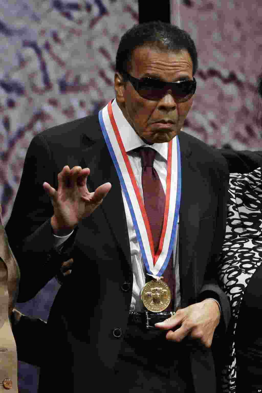 រូបឯកសារ៖ ជើងឯកកីឡាប្រដាល់លោក Muhammad Ali ចូលនិវត្តន៍បក់ដៃ បន្ទាប់ពីលោកបានទទួលមេដាយ Liberty Medal សម្រាប់ស្នាដៃមនុស្សធម៌ នៅអំឡុងពិធីមួយនៅឯ National Constitution Center កាលពីថ្ងៃព្រហស្បតិ៍ កាលពីថ្ងៃទី១៣ ខែកញ្ញា ឆ្នាំ២០១២ នៅក្រុង Philadelphia។