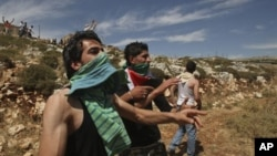 Người dân Palestine ném đá về phía binh sĩ Israel. Họ nói họ ngăn không cho những người định cư Israel tắm ở bể chứa nước người Palestine dùng để trồng trọt, canh tác