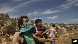 Palestinians throw stones at Israeli troops during clashes in the West Bank village of Iraq Burin, near Nablus, 15 May 2010 (file photo). Residents of the village said they are trying to prevent Jewish settlers from bathing in a water cistern Palestinian