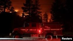 Sebuah mobil pemadan kebakaran terlihat di tengah kebakaran Caldor yang melahap deretan pepohonan di Christmas Valley, dekat South Lake Tahoe, California, AS, 31 Agustus 2021. (REUTERS/Brittany Hosea-Small)