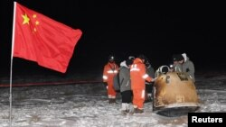 Researchers work around Chang'e-5 lunar return capsule carrying moon samples next to a Chinese national flag, after it landed in northern China's Inner Mongolia Autonomous Region, December 17, 2020.
