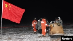 Researchers work around Chang'e-5 lunar return capsule carrying moon samples next to a Chinese national flag, after it landed in northern China's Inner Mongolia Autonomous Region, December 17, 2020. (China Daily via REUTERS)