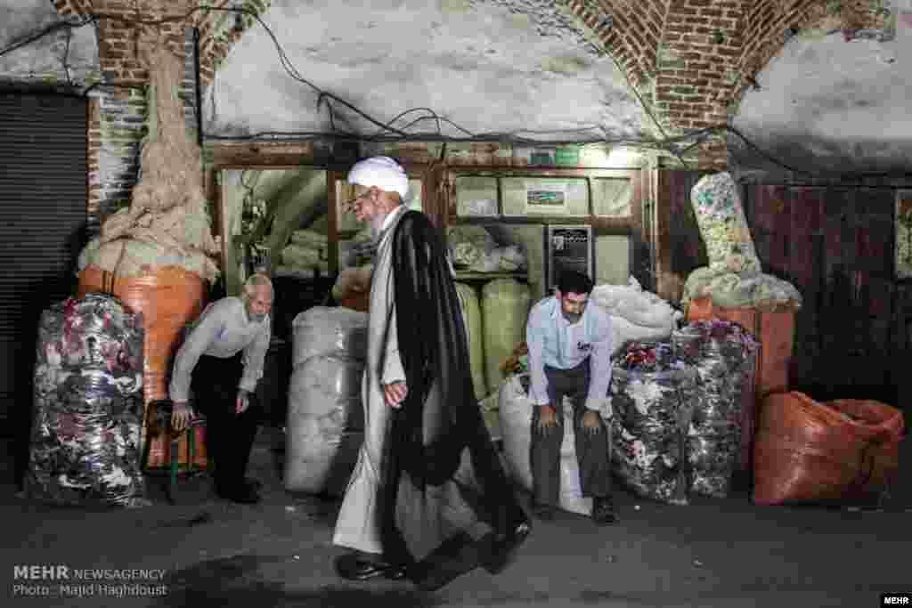 """دو کاسب به احترام مرد روحانی نیم خیز می شوند. خبرگزاری مهر عکسهایی با عنوان """"زندگی روزمره و محیط پیرامون در شهر تبریز:"""" منتشر کرده است. عکس: مجید حقدوست، مهر"""