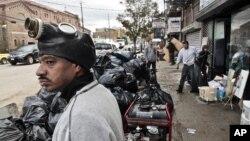 Ông Raymond Palermo giúp dọn dẹp tại cửa hàng điện tử của người em họ ở Brooklyn, New York sau trận bão
