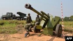 Des soldats des forces armées de la République démocratique du Congo (FARDC) installent une pièce d'artillerie mobile à côté d'un lance-roquettes multiples mobile à Matombo, Beni, Nord Kivu, le 13 janvier 2018.