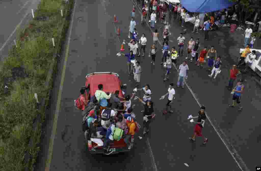 미국으로 향하는 중남미 이민자들이 멕시코소칠테펙을 지나는 가운데 종교 단체 직원들이 물, 휴지, 기저귀, 약 등이 든 작은 가방을 이민자들에게 건네주고 있다.