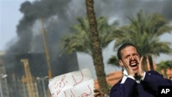 An Egyptian protester chant anti-government slogans, as another holds a sign in Arabic reading 'Voice of the People, no to Mubarak,' as smoke billows from the National Council for Women and Children's building, in downtown Cairo, January 29, 2011