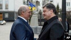 Ukrainian President Petro Poroshenko, right, welcomes Belarusian President Alexander Lukashenko during their meeting in Kyiv, Ukraine, Dec. 21, 2014.