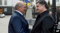 Presiden Ukraina Petro Poroshenko (kanan) menyambut kunjungan Presiden Belarus, Alexander Lukashenko di Kyiv, Ukraina hari Minggu (21/12).