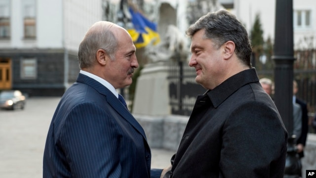 Ukrainian President Petro Poroshenko, right, welcomes Belarusian President Alexander Lukashenko during their meeting  in Kyiv, Ukraine, Dec. 21, 2014.