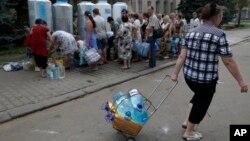 Cư dân địa phương xếp hàng để lấy nước trên đường phố ở Donetsk, miền đông Ukraine, ngày 13/7/2015.