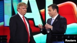 Republican U.S. presidential candidate Donald Trump (L) talks with rival Ted Cruz during a commercial break in the midst of the Republican U.S. presidential candidates debate sponsored by CNN at the University of Miami in Miami, Florida, March 10, 2016.