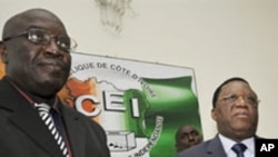 Le directeur du cabinet du premier ministre Sorok, Paul Koffi et le président de la CEI, Youssouf Bakayoko présentant la nouvelle liste électorale provisoire.